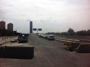 图为:京津桥尚未修好,不少司机把车开上桥停放。 来源:天津网-城市快报 摄影/韩爱青