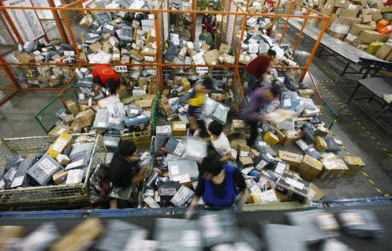 11月11日晚,在圆通快递转运中心,工人们在堆积如山的包裹中进行分拣工作。